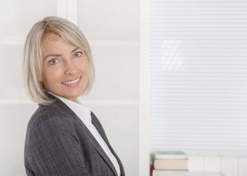 Attractive smiling senior business woman in portrait wearing blazer and blouse.